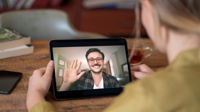 Person holding a tablet showing a person smiling and waving